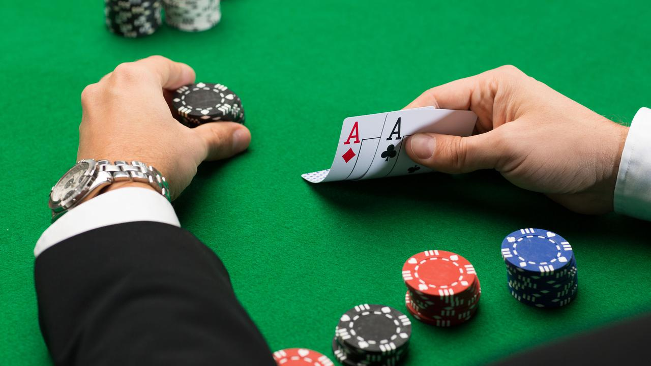 a pair of hands holding poker chips and cards on a casino table