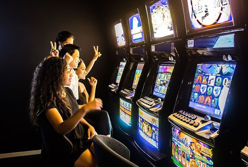 a group of people playing slots