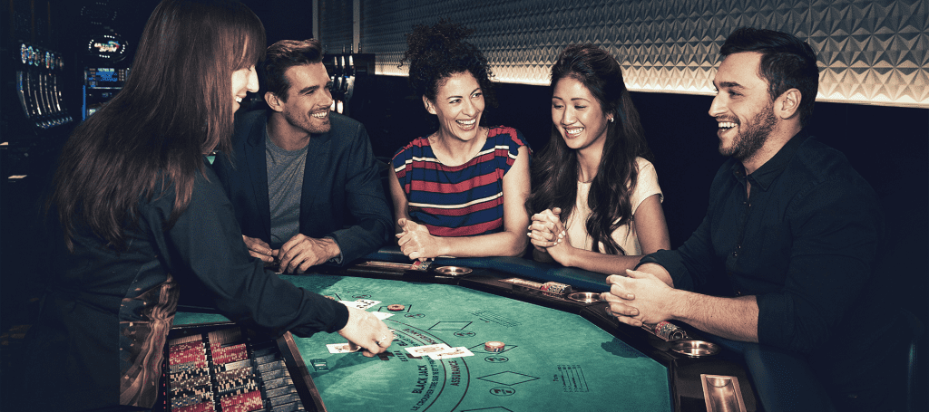 group of people smiling around a blackjack table