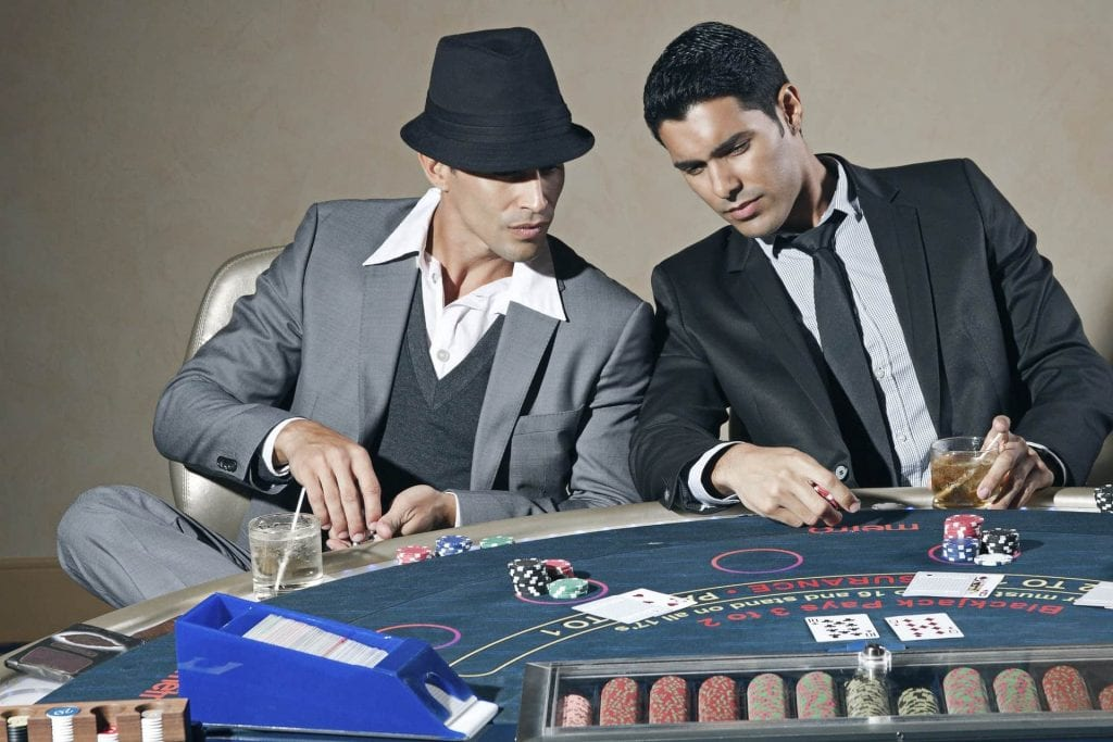 two men sitting in front of a casino table